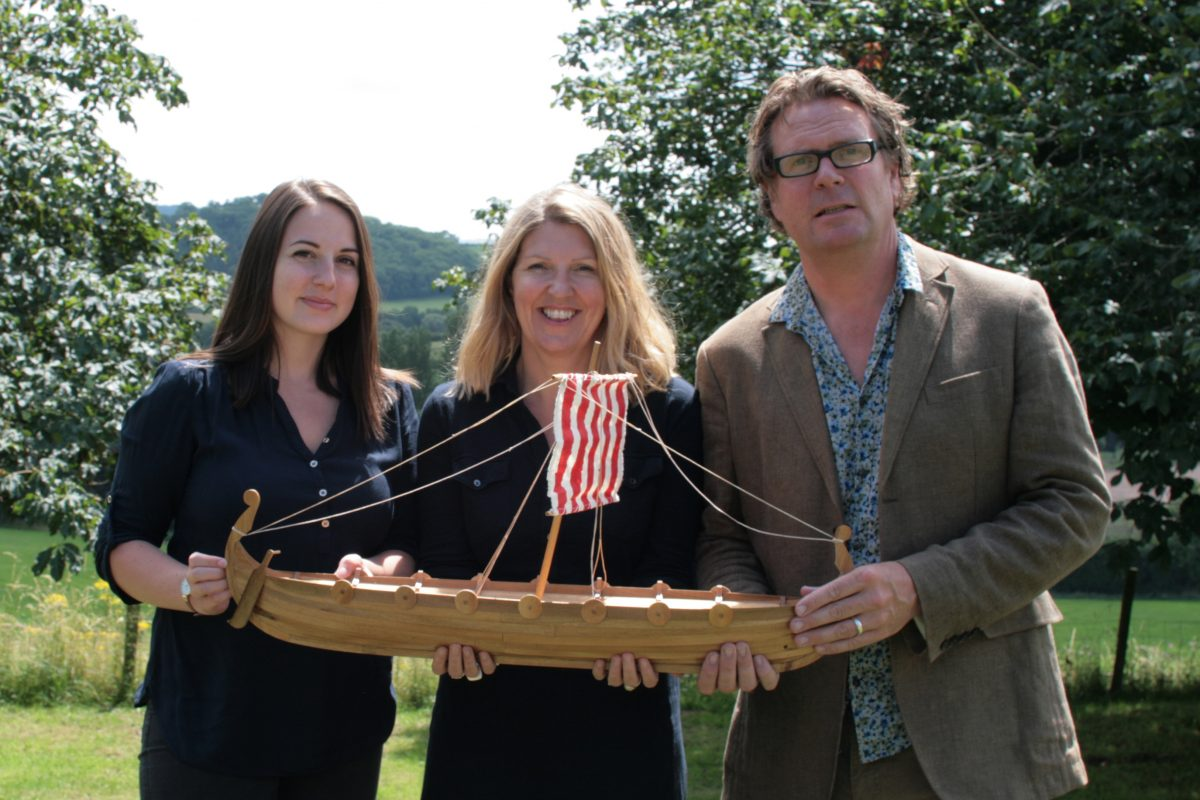 The team from Scattering Ashes hold up a mini Viking funeral boat.