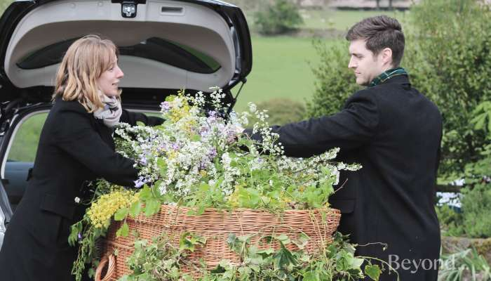 The team at Full Circle Funerals decorate a wicker casket.