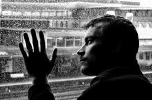 A grieving man looks out of a window